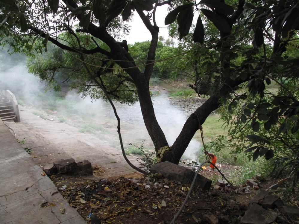 A sadhu busily burns plastic garbage before breakfast.